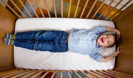 stretched: Portrait of happy cute boy lying in a baby cot with his arms and legs stretched