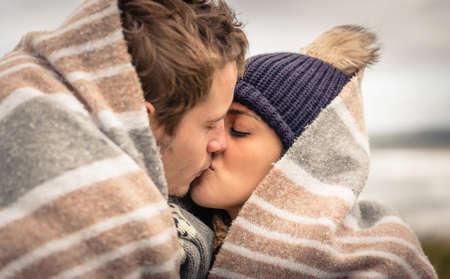 Close up do jovem casal bonito se beijando sob o cobertor em um dia frio, com mar e céu nebuloso escuro no fundo