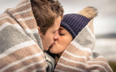 winter woman: Closeup of young beautiful couple kissing under blanket in a cold day with sea and dark cloudy sky on the background