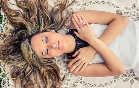 gestos: Retrato de la hermosa joven que cubre su cuerpo con los brazos cruzados que mienten en el suelo