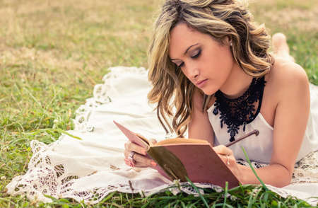 Portrait of romantic young woman writing in a diary lying down over the grass. Relax outdoor time concept. Stock Photo