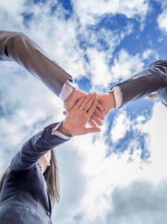 manos unidas: Vista inferior del equipo de negocios que muestra la unidad con las manos juntas sobre fondo de cielo azul