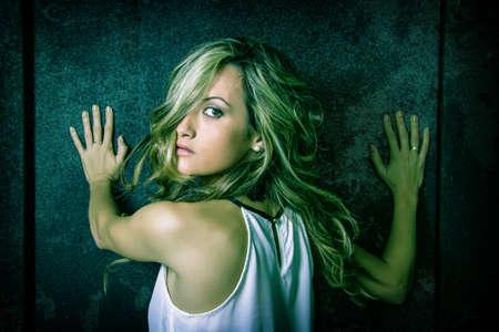 Closeup of young beautiful woman scared with her hands over a metallic dark door photo