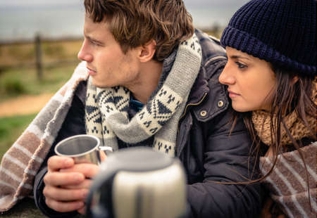 Closeup of young beautiful couple under blanket having hot beverage in a cold day with dark cloudy sky on the background photo