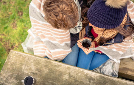 View from above of young couple under striped blanket having hot beverage outdoors in a cold day photo