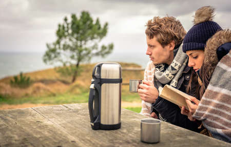 thermos: Portrait of young beautiful couple reading book under blanket in a Day With Either cold and dark cloudy sky on the background Stock Photo