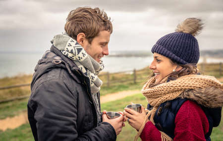 thermos: Portrait of young happy couple holding cups of hot beverage in a Day With Either cold and dark cloudy sky on the background