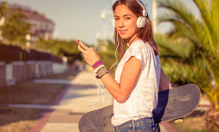 Portrait of beautiful young girl with skateboard and headphones listening music in her smartphone outdoors. Warm tones edition. Stock Photo