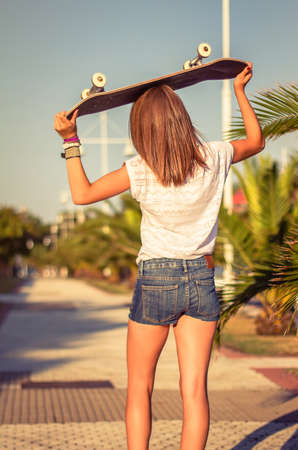 short shorts: Back view of beautiful young girl with short shorts and skateboard outdoors on a hot summer day. Warm tones edition.