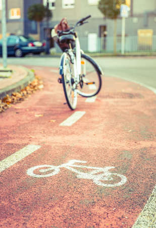bike lane: Bicycle road symbol over a street bike lane in autumn with white bicycle on the background