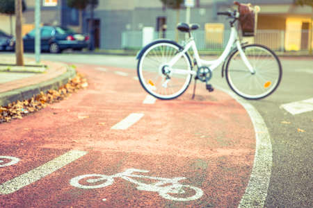 bicycle lane: Bicycle road symbol over a street bike lane in autumn with white bicycle on the background