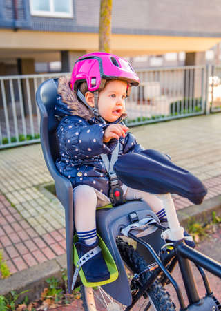 helmet seat: little girl with security helmet on the head sitting in bike seat Stock Photo
