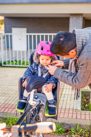 helmet seat: Portrait of father closing bicycle security helmet to her little daughter sitting in bike seat