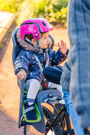 helmet seat: Portrait of little girl with security helmet on the head sitting in a bike seat behind of her father