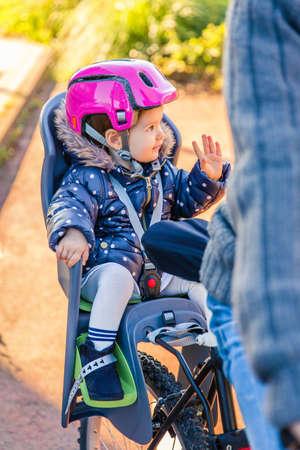 niños en bicicleta: Retrato de la niña con el casco de seguridad en la cabeza sentado en un asiento de la bicicleta detrás de su padre Foto de archivo