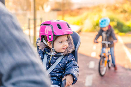 helmet seat: Portrait of little girl with security helmet on the head sitting in bike seat and her brother with bicycle on the background