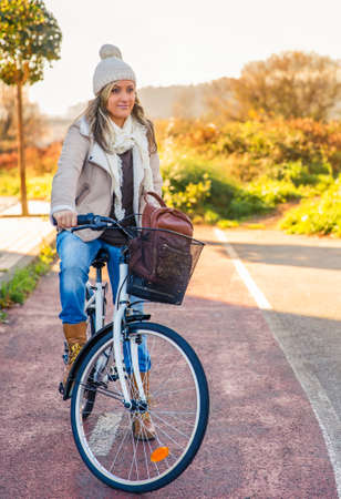 cycleway: Portrait of beautiful young woman stit over bicycle in a street bike lane on sunny winter day