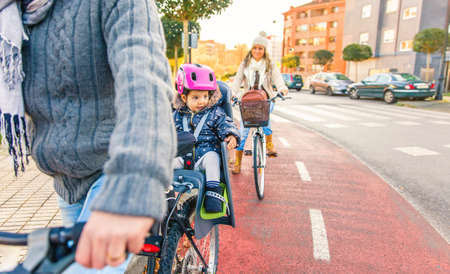 helmet seat: Portrait of little girl with security helmet on the head sitting in bike seat and her mother with bicycle on the background. Safe and child protection concept.