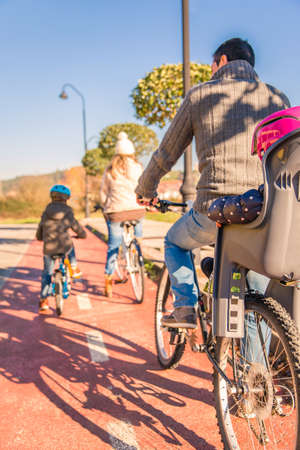 cycleway: Back view of happy family with children riding bicycles by the nature on a sunny winter day. Focus on father and baby seat. Stock Photo