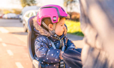 helmet seat: Portrait of little girl with security helmet on the head sitting in a bike seat behind of her father. Safe and child protection concept.