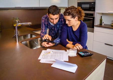 Ernstige jonge paar herziening van hun bankrekeningen met een digitale tablet en rekenmachine thuis. Financiële familie concept.
