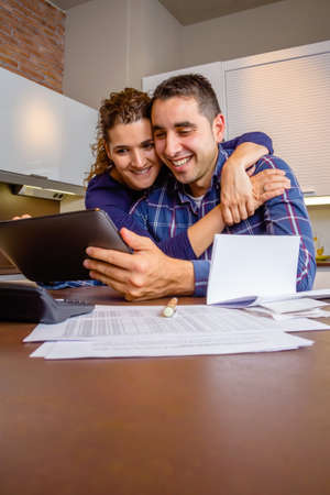 Vidám fiatal pár a digitális tábla a konyhában haza a munkát. Családi szabadidős otthon koncepció. Stock fotó