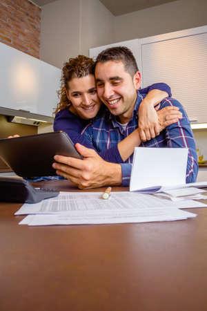 Vrolijke jong koppel met behulp van digitale tablet in de keuken thuis na het werk. Familie recreatie huis concept. Stockfoto