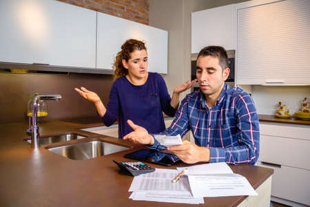 problem: Unemployed young couple with many debts reviewing their bills. Financial family problems concept. Stock Photo