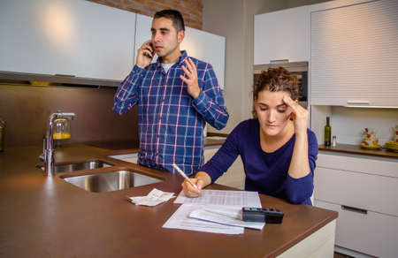 Angry young man arguing at phone while a woman calculating their bank credit lines. Financial family problems concept.