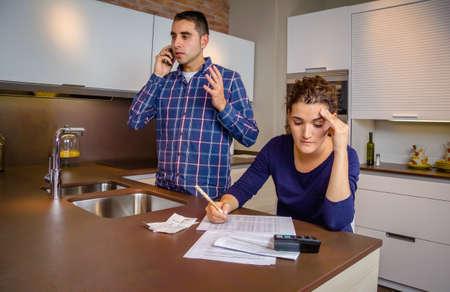 Hombre joven enojado argumentando en el teléfono, mientras que una mujer de calcular sus líneas de crédito bancarias. Concepto financiero de los problemas familiares.
