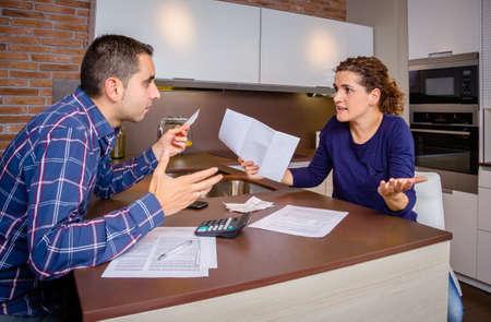 problemas familiares: Pareja joven enojada argumentando en casa por sus muchas deudas de tarjetas de cr�dito. Concepto financiero de los problemas familiares.