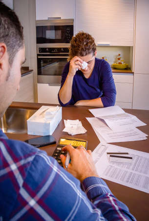 family problems: Young unemployed husband reviewing the bills and his desperate wife crying by their debts. Financial family problems concept.