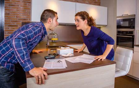 problemas familiares: Pareja joven enojado gritando en una pelea dif�cil por sus muchas deudas en casa. Concepto financiero de los problemas familiares. Foto de archivo