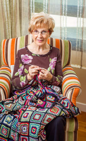 bedcover: Portrait of senior woman knitting a vintage wool quilt with colorful patches