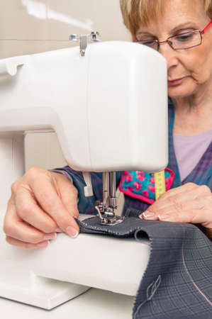 seamstress: Senior seamstress woman working with clothing item on a sewing machine Stock Photo