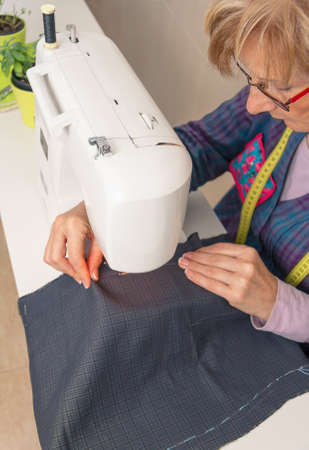 sewing item: Senior seamstress woman working with clothing item on a sewing machine. Selective focus on woman face. Stock Photo