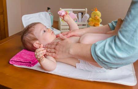 Mãe massageando corpo de adorável bebê deitado após a mudança de fralda
