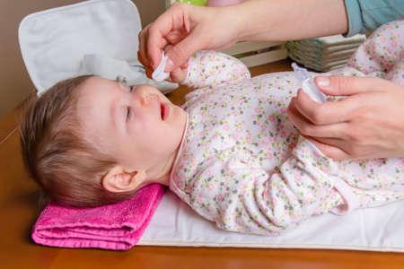 physiological: Madre enojados ojos del beb� de limpieza con suero fisiol�gico en un algod�n