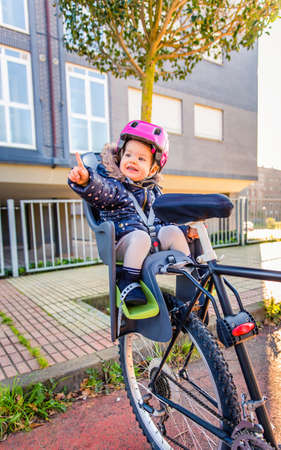 helmet seat: Portrait of little girl with security helmet on the head sitting in bike seat ready to take a walk. Safe and child protection concept.