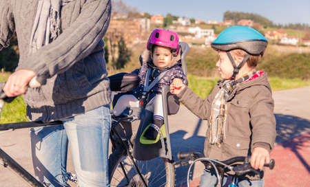 helmet seat: Portrait of little girl with security helmet on the head sitting in bike seat and shaking hand of her brother. Safe and child protection concept.