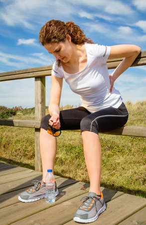 자연 배경 위에 고통스러운 부상에 의해 그녀의 허리 근육을 만지고 앉아 운동복에 체육 젊은 여자. 스포츠 부상 개념입니다.