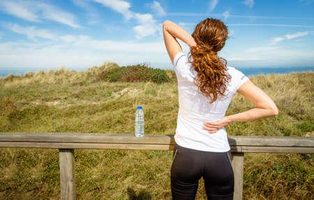 dolor muscular: Volver la vista de mujer joven atlético en ropa deportiva que toca su cuello y músculos de la espalda por una lesión dolorosa, sobre un fondo de naturaleza. Lesiones deportivas concepto.