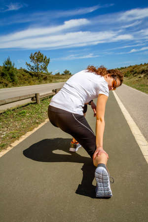 Back view of athletic young woman with sportswear suffering pain in her leg calf by a muscle cramp on a training. Sport injuries concept.