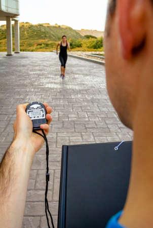 타이밍에 크로노 미터를 사용하여 남자 트레이너 손의 근접 촬영 운동 젊은 여성이 힘든 훈련을 야외에서 스톡 콘텐츠