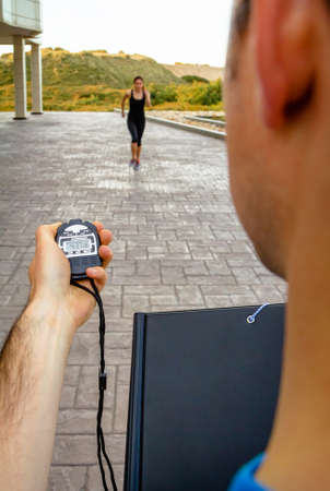 Closeup of man trainer hand using a chronometer to timing athletic young woman in a hard training outdoors