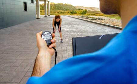 deportista: Primer del hombre entrenador mano utilizando un cron�metro para sincronizaci�n con la cansada mujer joven atl�tico en un duro entrenamiento al aire libre