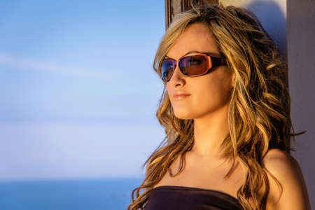 Portrait of beautiful curly blonde girl with black top and sunglasses posing over a nature background photo