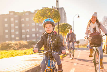 Happy family with a child riding bicycles by the city on a sunny winter day