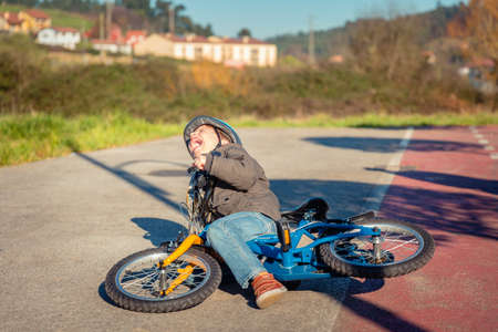 falling: Boy crying and screaming in the street ground after falling off to his bicycle