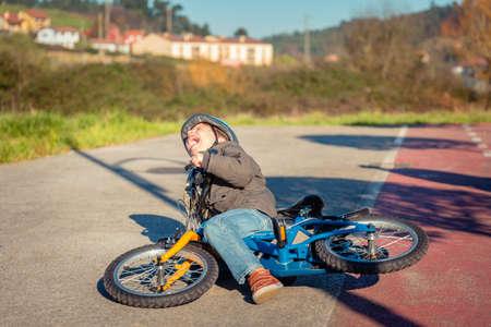Boy piangere e urlare nel terreno strada dopo essere caduto a sua bicicletta